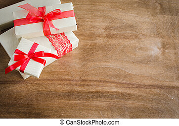 Vintage gift boxes with red bow ribbon on wooden background.