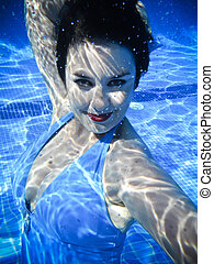 Vintage girl swimming and smiling underwater in a swimming pool