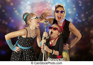 Vintage girls posing with microphone