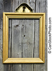 vintage golden wooden picture frame on old wooden wall
