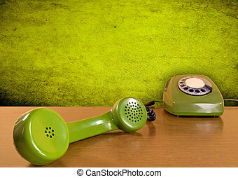 green telephone on the wooden table