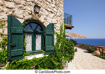 Vintage green window on a brick house with ocean background, Greece