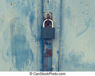 Vintage grundge aged padlock. Old blue lock hanging on blue garage door.