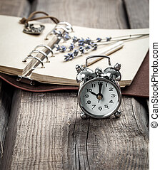 Vintage grunge still life with watch, and old book and pencil.