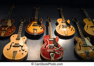 Vintage Guitars - A wall with vintage guitars hanging on...