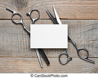 Vintage hairdressing scissors and blank business card on wooden table