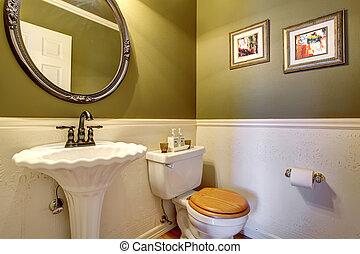 Vintage half bathroom with green walls.