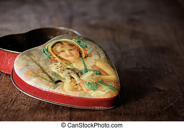 Vintage heart shaped tin box on wooden table