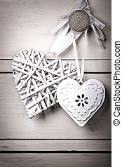 A wicker and a tin heart hanging from the knob of a chest of drawers. Vintage effect with intentional vignette.