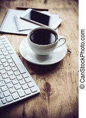 Vintage hipster style office table decor with cup of coffee, computer keyboard and smart phone. Blogger's modern workspace, interior details with copy space.
