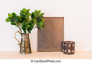 Vintage home decor composition with metal objects and green plant