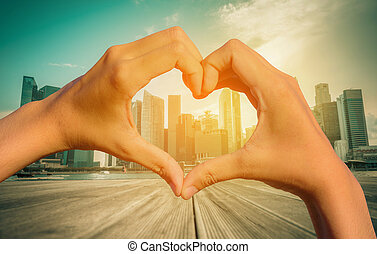 Vintage image of Heart Shaped Hand with blurred Singapore city skyline.