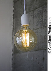 Vintage incandescent Edison type bulb on grey wall