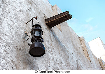 Vintage kerosene lamp on the white wall of a dilapidated building