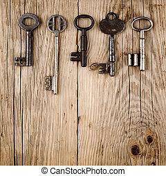 Vintage keys on old wooden background