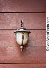 Vintage lamp hit on wooden wall.