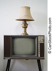 Vintage lamp on top of television in white room