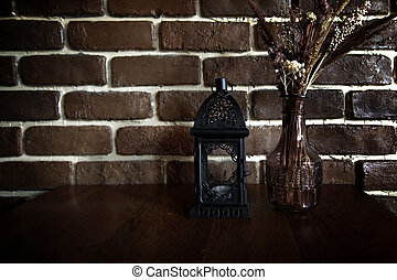 vintage lantern lamp ad flower vase on table with brick wall background