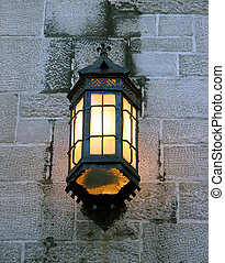 Vintage lantern on a stone wall of an old building