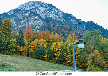 Vintage lantern on the background of the Alps and autumn yellow forest in Bavaria