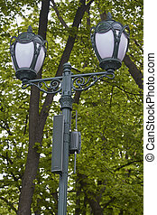 Vintage lantern with surveillance camera in public park, selective focus