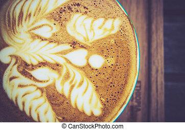 vintage latte art coffee cup on wood background