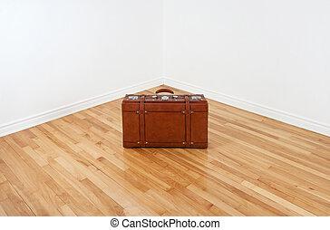 Vintage leather suitcase in empty room corner