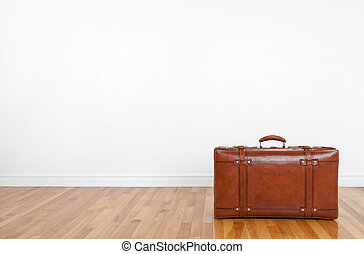 Vintage leather suitcase on a wooden floor