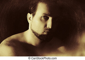 vintage-like low key portrait of young man with beard and...