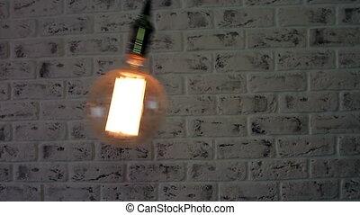 Vintage Loft lamp swinging on a brick wall