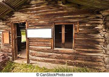 Vintage log cabin with empty sign - Ruin of old cabin with...