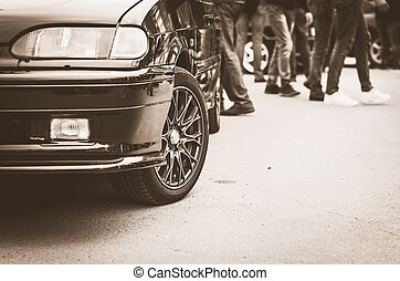 Vintage Low Angle View of a Car Front with Blurred People Walking In Background.