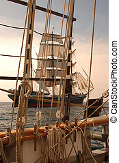 Vintage windjammer seen through the rigging of another vintage wooden ship