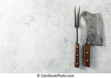 Vintage Meat cleaver and BBQ fork on a empty grey background.