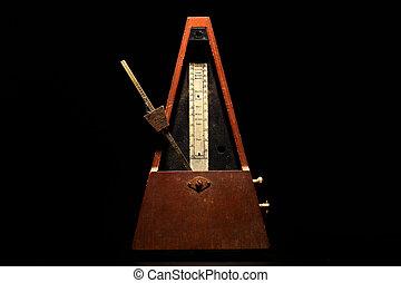Horizontal shot of a vintage metronome, on a black background.
