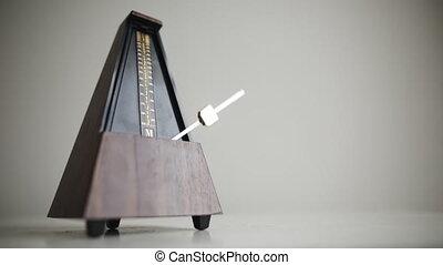 Vintage metronome with golden pendulum beats slow rhythm on the gray background