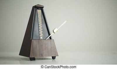 Vintage metronome with golden pendulum beats slow rhythm on the gray background