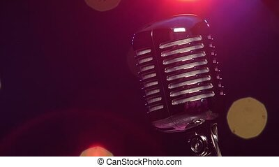 Vintage microphone against dark blurry background with bright flashing lights