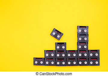 Vintage mini DV cassette tapes used for filming back in a day. Pattern made of plastic video tapes on yellow background