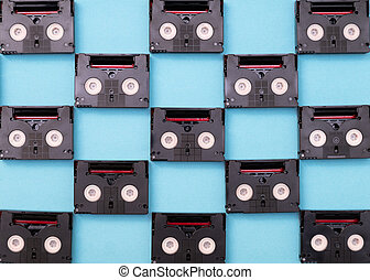 Vintage mini DV cassette tapes used for filming back in a day. Pattern made of plastic video tapes on blue background