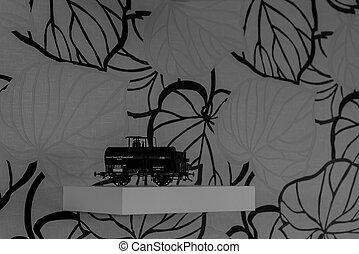 Vintage model tank wagon on shelf, monochrome