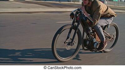 Vintage Motorbiker - Boy on vintage motorcycle riding down...