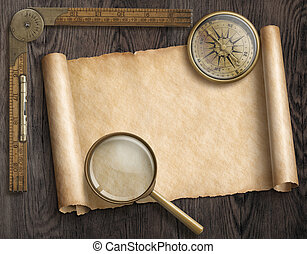 vintage nautical compass and loupe on table with treasure map scroll