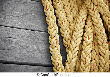 Vintage nautical knots background with copy-space. Big marine sea ropes on wooden desk