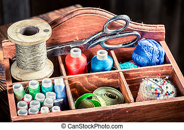 Vintage needle, threads and scissors on tailor table