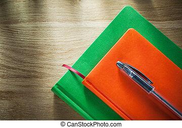 Vintage notebooks pen on wooden board education concept