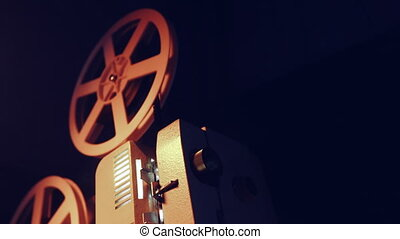 Vintage objects, cinematograph concept. Retro film projector playing in the dark room. Old-fashioned antique super 8mm film projector projecting beam of light. 4k.