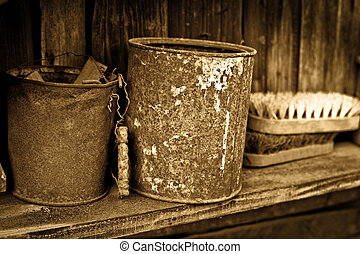 Vintage objects - two rusty greasy cans on wooden shelf