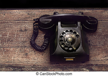 vintage old black rotary phone with dust and scratches on wooden table background