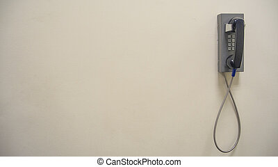 Vintage old phone mounted on a white wall